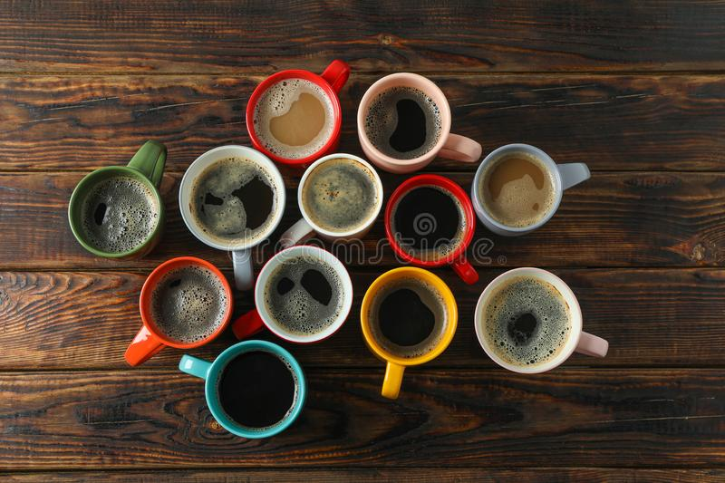 Multicolored cups of coffee on wooden background, top view royalty free stock photos