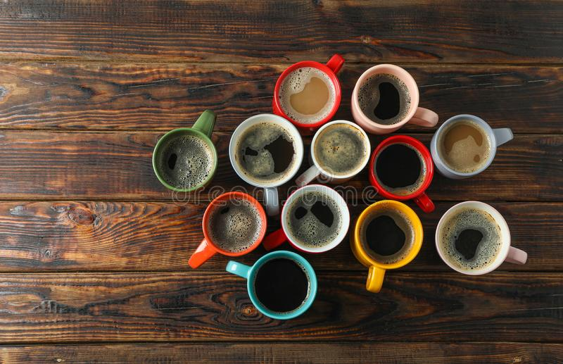 Multicolored cups of coffee on wooden background, top view royalty free stock images
