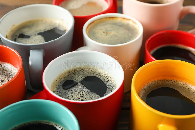 Multicolored cups of coffee on wooden table as background stock photo