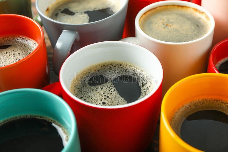 Multicolored cups of coffee on wooden table as background stock photos
