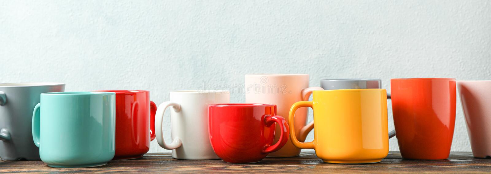 Multicolored cups on wooden table against light background stock images