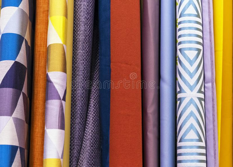 Multicolored curtain designs in a retail store window. Samples of the texture of multi-colored fabrics royalty free stock photo
