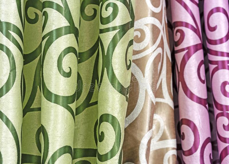 Multicolored curtain designs in a retail store window. Samples of the texture of multi-colored fabrics.  stock images
