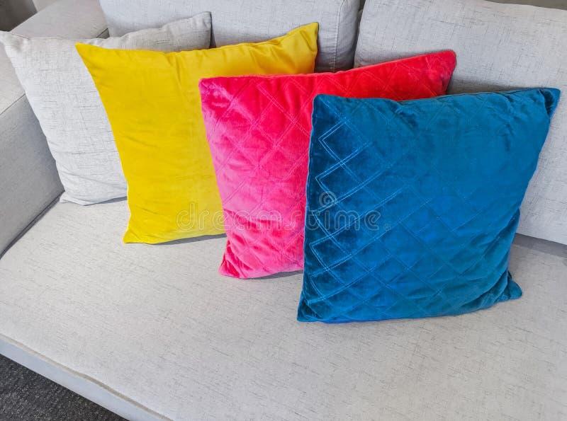 Multicolored cushions decorating a gray sofa. Bright multicolored cushions decorating a simple gray sofa stock photo