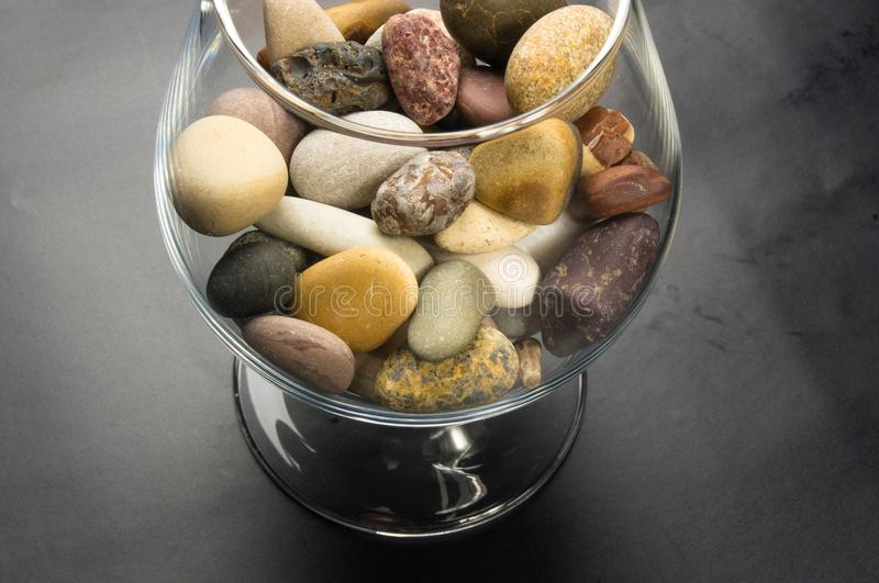Decorative pebbles in glass containers. Multicolored decorative pebbles in glass containers on a black background royalty free stock photos