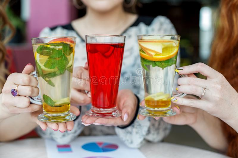 Multicolored delicious cocktails in female hands. Concept of drinks, meeting, fun and party stock image