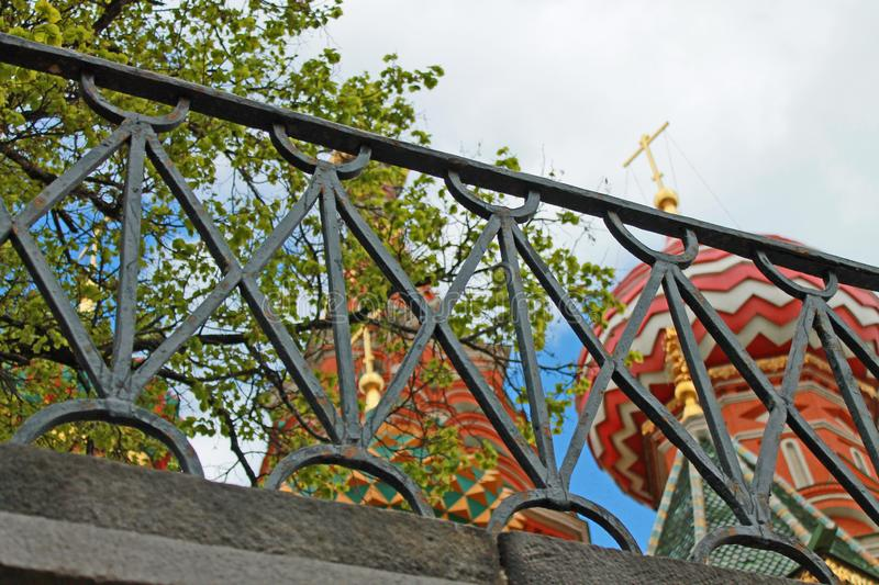 Multicolored domes of St. Basil`s Cathedral in Moscow Russia through the lattice of the black fence stock photography