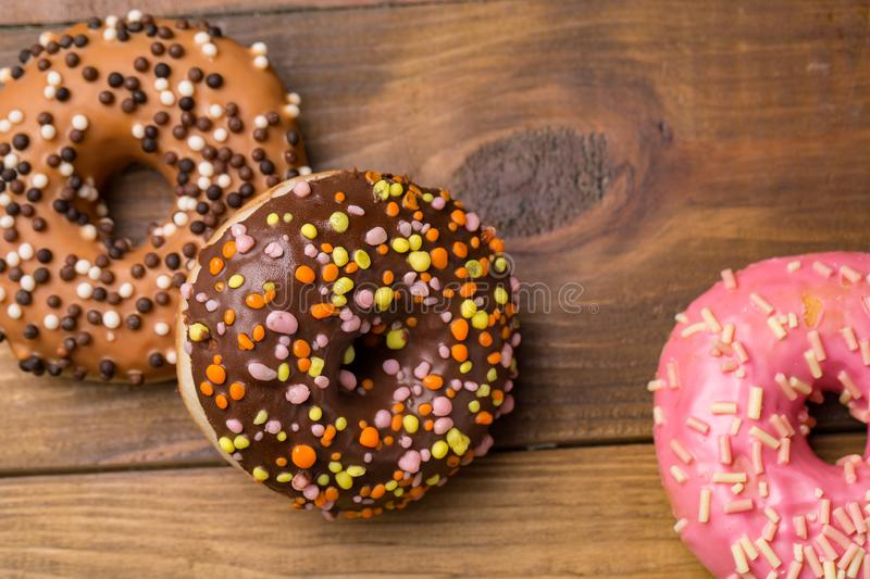 Multicolored Donuts on wooden background. sweets for breakfast stock photography