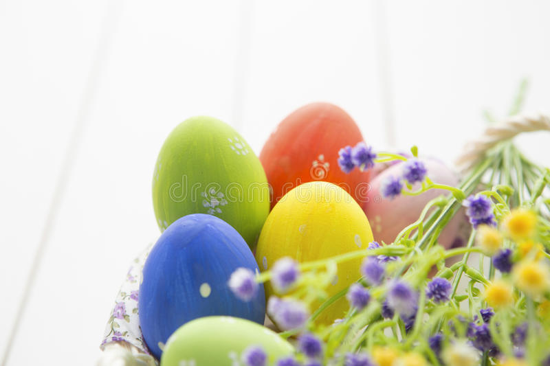 Multicolored easter eggs in basket with flowers royalty free stock images