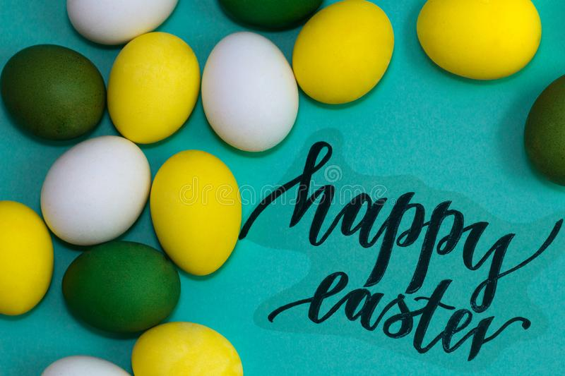 Multicolored easter eggs on turquoise background, black inscription Happy Easter stock photos