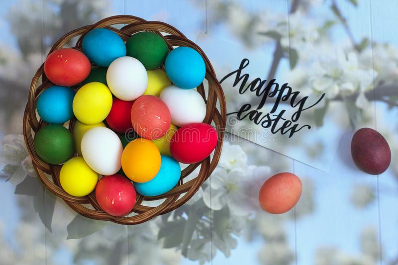 Multicolored easter eggs in a wicker basket on a wooden white background, inscription Happy Easter royalty free stock photography