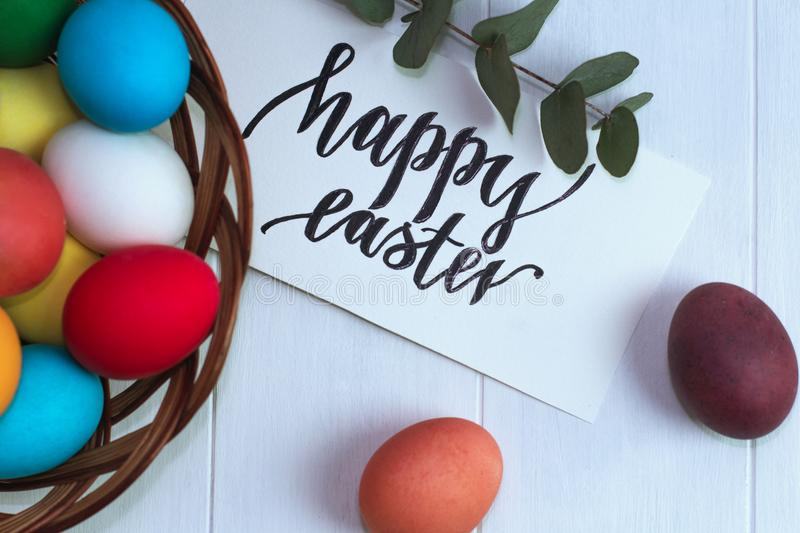 Multicolored easter eggs in a wicker basket on a wooden white background, inscription Happy Easter royalty free stock photo