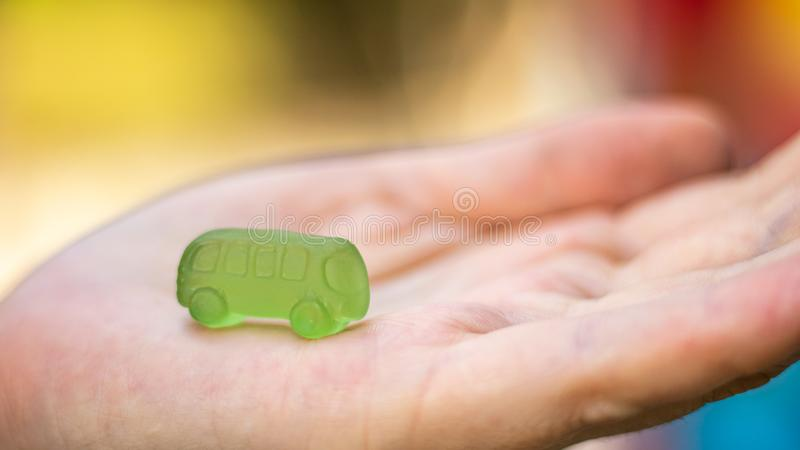 Multicolored edible cars from marmalade on a children`s palm. Business idea for obtaining a mortgage or bank credit loan. royalty free stock photography