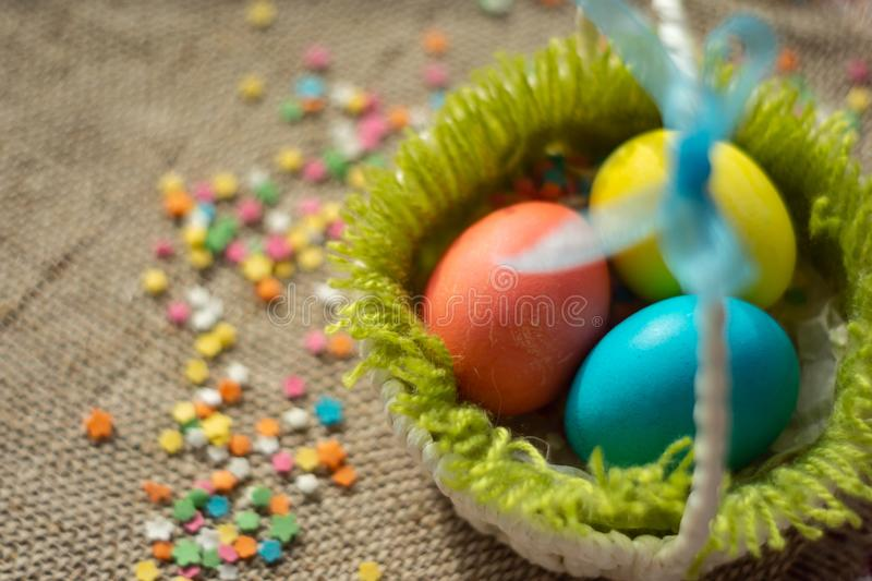 Multicolored eggs in easter festive basket on canvas napkin royalty free stock photo