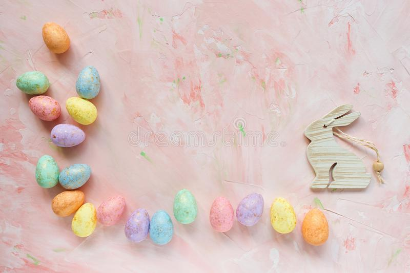 Multicolored eggs and rabbit decoration on a pink background. Easter celebration concept. royalty free stock image