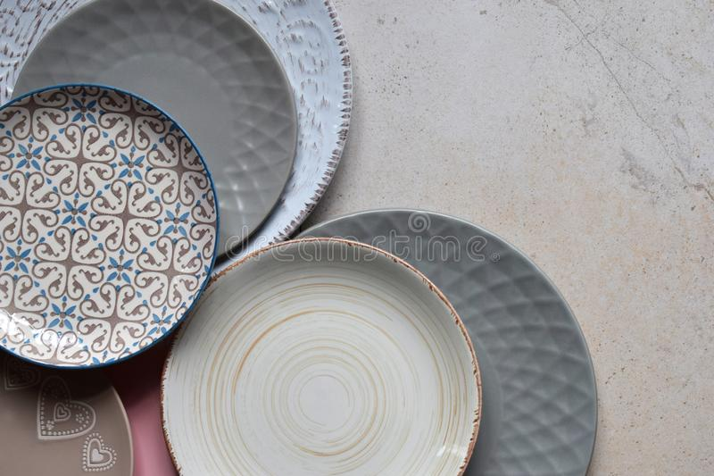 Multicolored empty ceramic plates and bowls on a marble background. Table setting. Shabby chic or retro style. Copy space. Mock up royalty free stock image