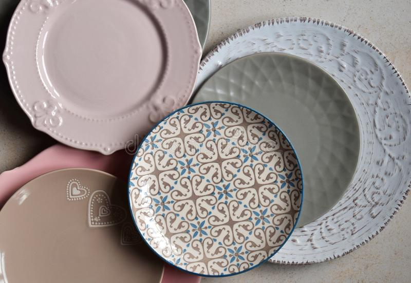 Multicolored empty ceramic plates and bowls on a marble background. Table setting. Shabby chic or retro style. Copy space. Mock up stock image