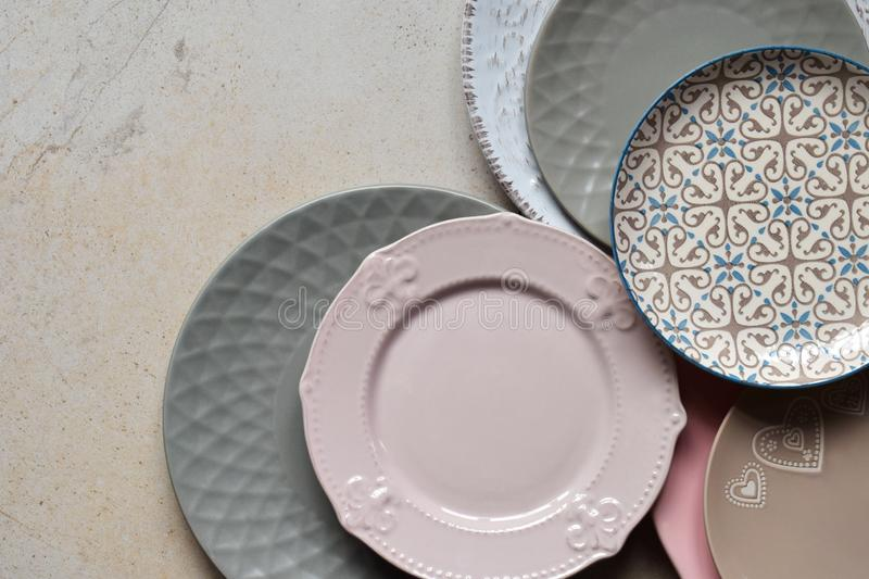 Multicolored empty ceramic plates and bowls on a marble background. Table setting. Shabby chic or retro style. Copy space. Mock up royalty free stock photos