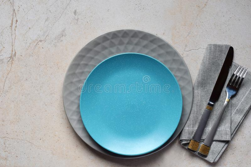 Multicolored empty ceramic plates and bowls on a marble background. Table setting. Shabby chic or retro style. Copy space. Mock up stock photos