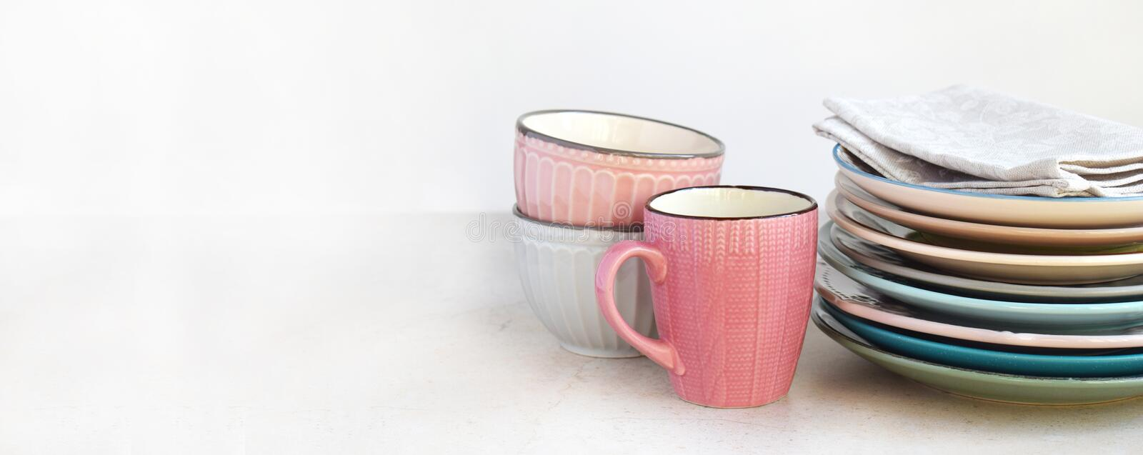 Multicolored empty ceramic plates, mugs and bowls on a marble background. Table setting banner. Shabby chic or retro style. Copy stock photography