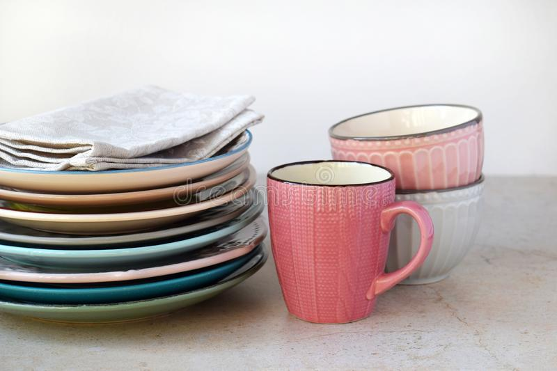 Multicolored empty ceramic plates, mugs and bowls on a marble background. Table setting. Shabby chic or retro style. Copy space. royalty free stock photos