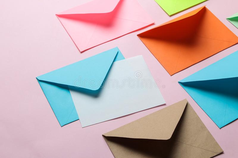 Multicolored envelope with blank for text on a bright trendy pink background. free space stock photography