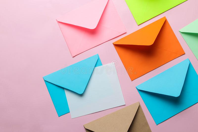 Multicolored envelope with blank for text on a bright trendy pink background. free space. top view royalty free stock image
