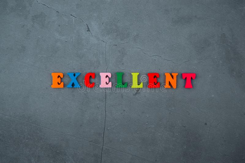 The multicolored excellent word is made of wooden letters on a grey plastered wall background.  stock images