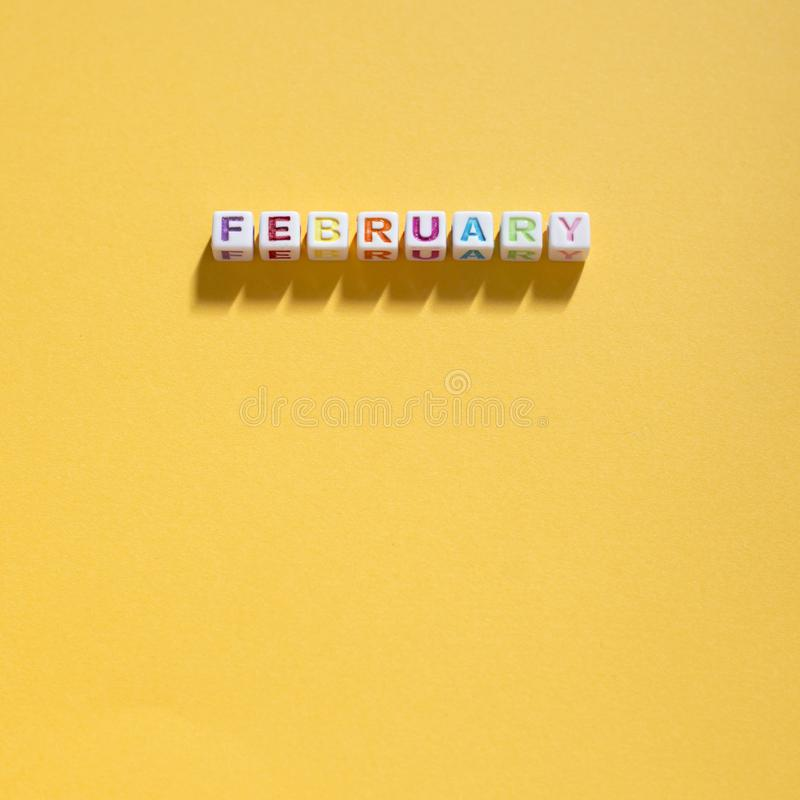 Multicolored February on a yellow background. Photograph of Multicolored February letter tiles / beads spelling February on a yellow background on a square stock images