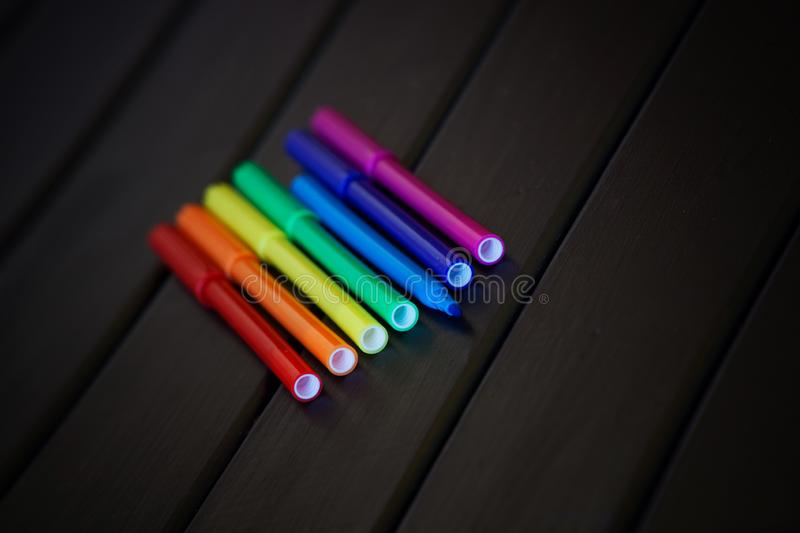 Multicolored felt pens are laid out in the color of the rainbow. LGBT symbols. Freedom of choice and creativity royalty free stock image