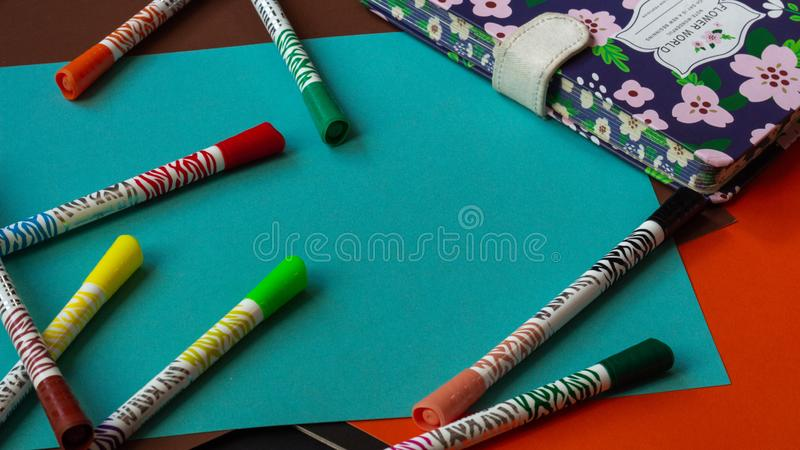 Multicolored felt-tip pens lie on colorful bright cardboard next to the notepad stock photo