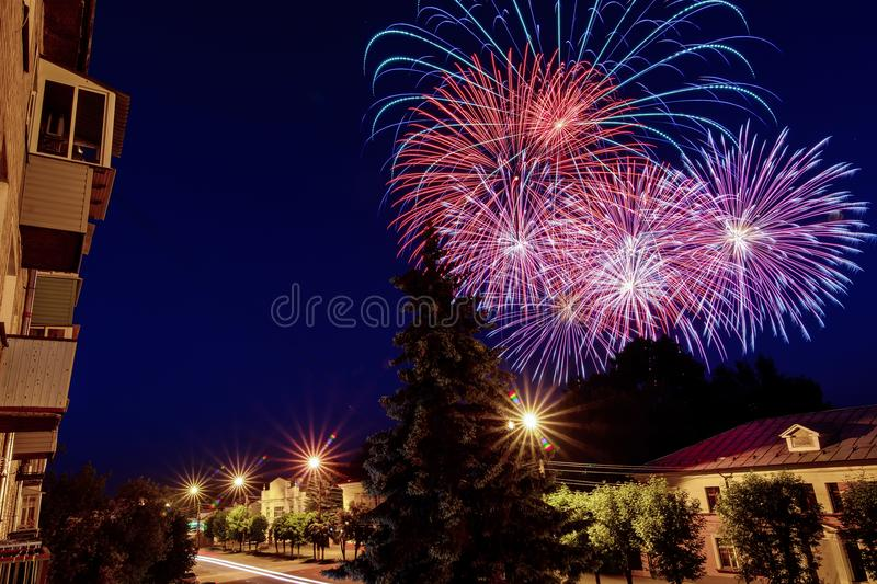 Multicolored fireworks on the holiday over the city against the night sky stock image