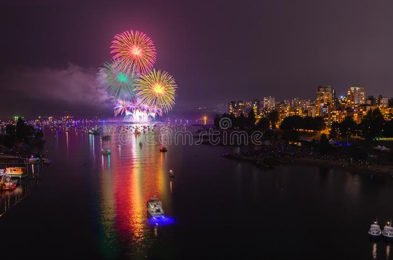 Multicolored fireworks lights over the ocean near the big city royalty free stock image