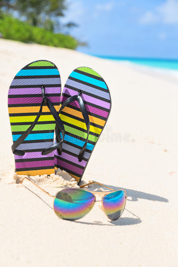 Multicolored flip-flops and sunglasses on a sunny beach..Tropical beach vacation and travel concept, vertical composition. Multicolored flip-flops and sunglasses stock photography