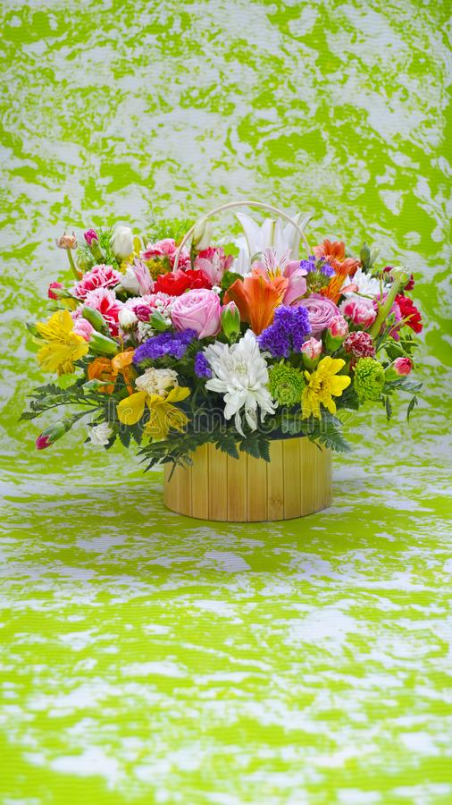 Multicolored flowers bouquet on green, marble stylised background. Multicolored flowers bouquet in yellow basket. Roses, carnations, lilies, chrysanthemums on stock images