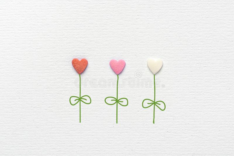 Multicolored Flowers in Heart Shape Made of Sugar Candy Sprinkles Hand Drawn Steams Leaves on White Watercolor Paper. Background. Creative Mixed Media Image royalty free stock photo