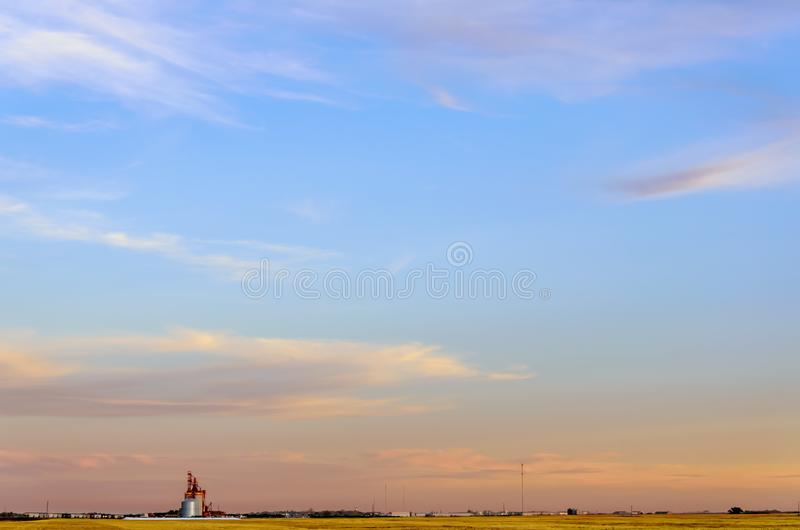 multicolored, fluffy tender cirrus clouds, yellow field, elevator and silver barns for grain stock photos