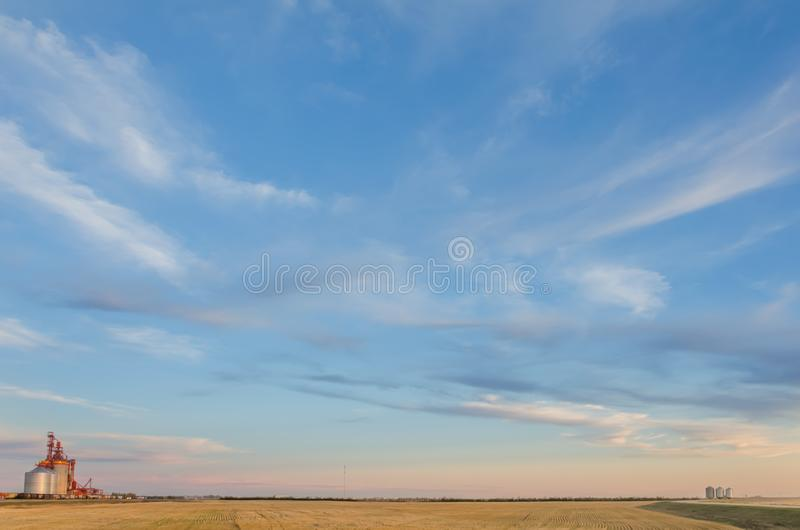 Sky with multicolored, fluffy, tender cirrus clouds, yellow field, granary and silver barns for grain royalty free stock photos