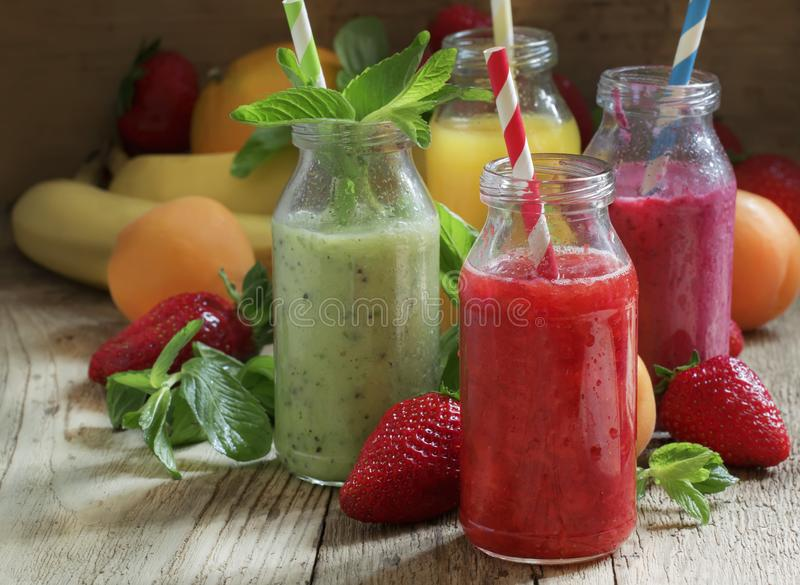 Multicolored fruit and berry smoothies, old wooden table, selective focus stock images