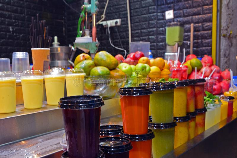 Multicolored fruit drinks and juice in plastic cups stand on the counter. market in jerusalem, israel royalty free stock photography
