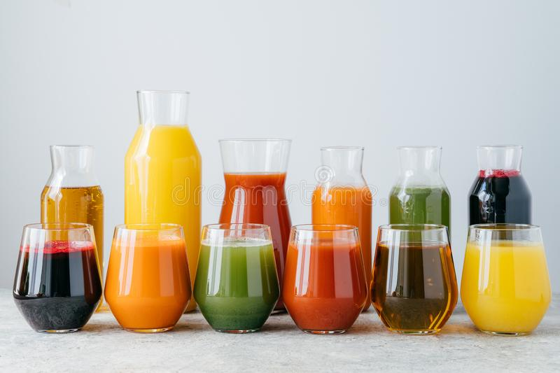 Multicolored fruit juice in glass jars  over white background. Drinks containing vitamins made of orange, pomegranate,. Carrot, spinach stock photos