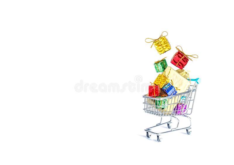 Multicolored gift boxes with beautiful golden bows fall into a gift-filled shopping cart isolated on a white royalty free stock images