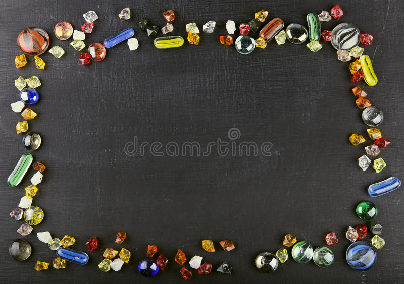 Multicolored glas marmeren ballen en glaskiezelstenen op zwarte surfa stock foto