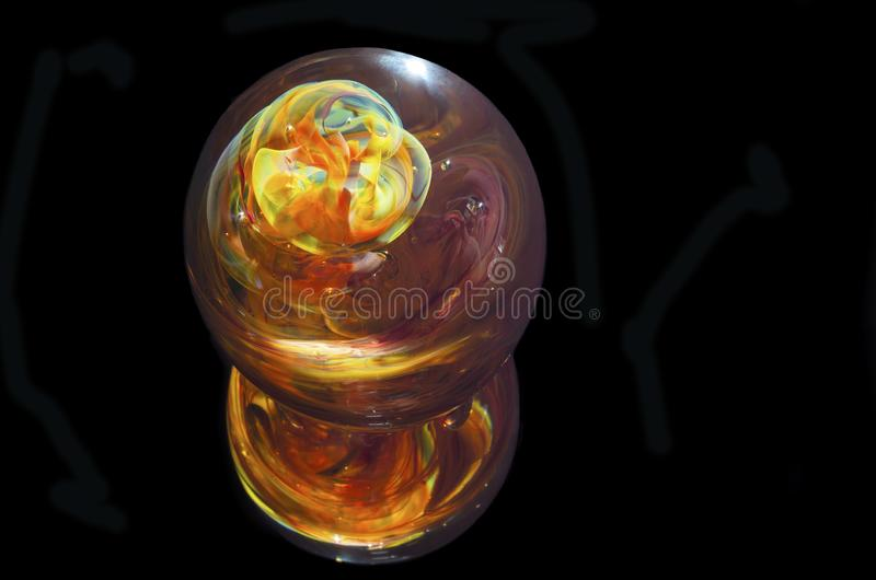 Multicolored Glass Paperweight Against Black. Multicolored glass paperweight and reflection isolated against black royalty free stock photos
