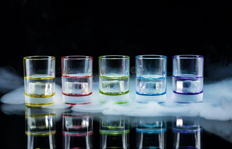 Multicolored glazen die met alcoholische dranken, met binnen ijsblokjes worden gevuld die, zich op de spiegeloppervlakte bevinden stock fotografie