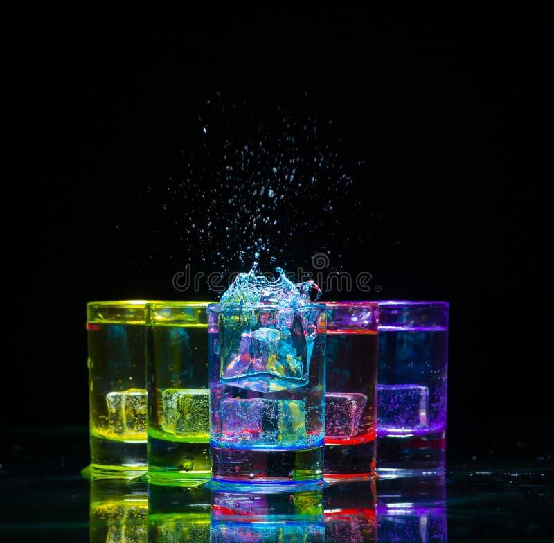 Multicolored glazen met alcoholische dranken, met splases die van ijsblokjes worden gevuld die binnen vallen, zich op de spiegelo royalty-vrije stock fotografie