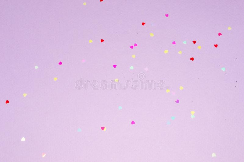 Multicolored glitter hearts on purple background in vintage colors stock images