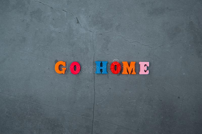 The multicolored go home word is made of wooden letters on a grey plastered wall background royalty free stock photography