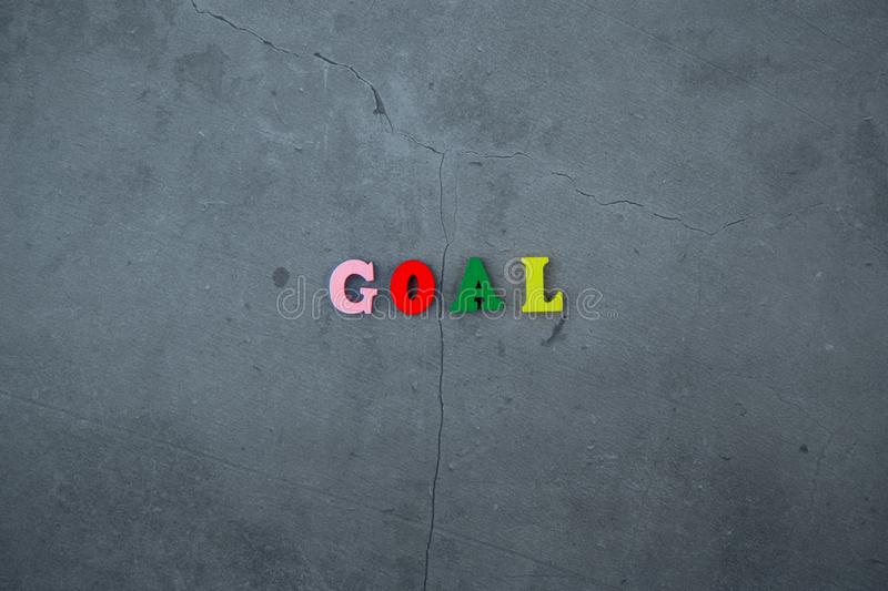 The multicolored goal word is made of wooden letters on a grey plastered wall background.  stock photo