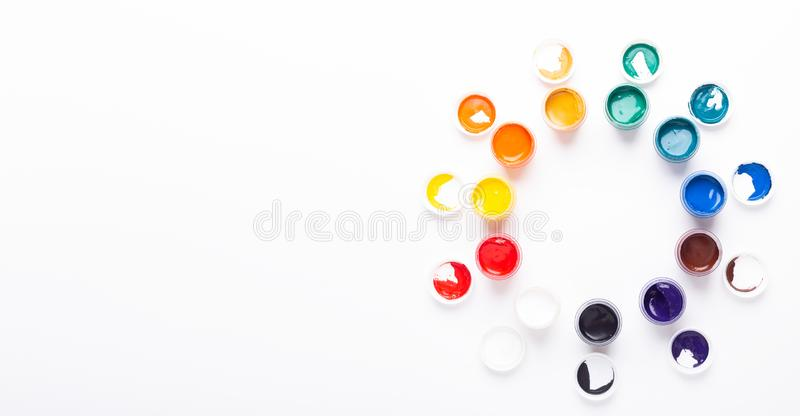 Multicolored gouache on a white background Circle shape Isolated Paints in containers Top view Banner Horizontal. Multicolored gouache on a white background stock photography
